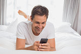 Young man text messaging in bed at home