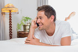 Casual relaxed man using mobile phone in bed