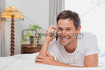 Casual man using mobile phone in bed