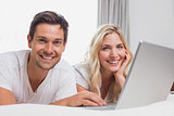 Relaxed young couple using laptop in bed