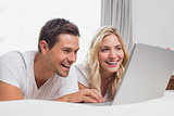 Cheerful relaxed couple using laptop in bed