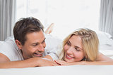 Close-up of a relaxed couple smiling in bed