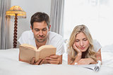 Relaxed couple reading books in bed