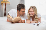Relaxed casual couple reading books in bed