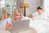 Woman using laptop while man reading book in bed