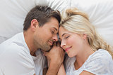 Loving couple lying in bed with eyes closed
