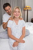Smiling man massaging woman's shoulders in bed
