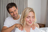 Smiling man massaging woman's shoulders