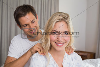 Smiling young man massaging woman's shoulders