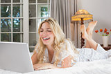 Cheerful casual woman using laptop in bed