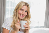 Beautiful casual young woman holding coffee cup