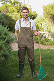 Young man in dungarees holding rake in garden