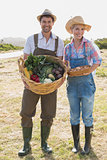 Smiling couple with vegetables standing in field