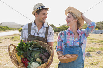 Smiling young couple with vegetables in field