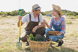 Smiling couple with vegetables in field