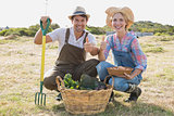 Couple with vegetables gesturing thumbs up in field