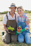 Smiling couple with potted plants in field