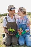 Smiling couple with potted plants in the field