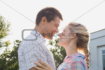 Young couple looking at each other against the sky