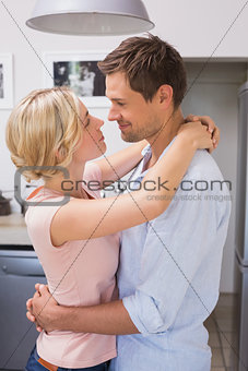 Loving young couple looking at each other at home