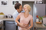 Cheerful man embracing woman from behind in kitchen