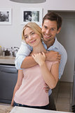 Young man embracing woman from behind in kitchen