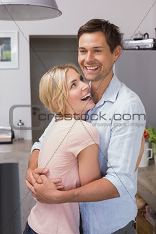 Happy young couple embracing in the kitchen