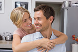 Woman embracing man from behind in kitchen
