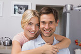 Smiling woman embracing man from behind in kitchen