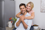 Smiling woman embracing man from behind at home
