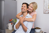 Cheerful woman embracing man from behind at home