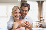 Happy man embracing woman from behind at home