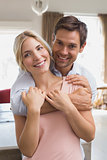 Man embracing woman from behind at home
