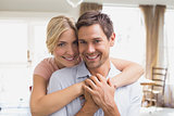 Woman embracing man from behind at home