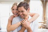 Happy woman embracing man from behind at home