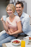 Man embracing woman at breakfast table at home