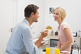 Couple looking at each other while having breakfast at home