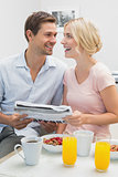 Couple reading newspaper while having breakfast at home