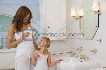 Mother and daughter with toothbrushes at bathroom washbasin