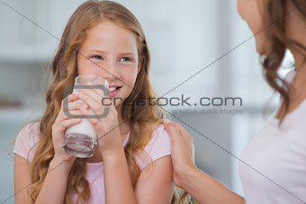Cute girl drinking milk as she looks to her mother