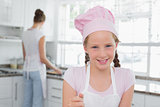 Close-up of a young girl wearing chef's hat in kitchen