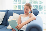 Relaxed girl reading a book on sofa in living room