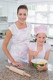 Young girl helping mother prepare food in kitchen