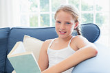 Relaxed girl reading book on sofa in living room