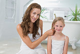 Smiling woman braiding cute little girl's hair in bathroom