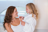 Mother and daughter with toothbrush in bathroom