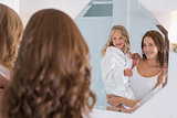Mother and daughter looking at bathroom mirror