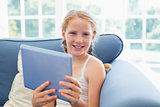 Young girl using digital tablet on sofa in living room