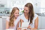 Mother showing a greeting card to daughter while having breakfast in kitchen