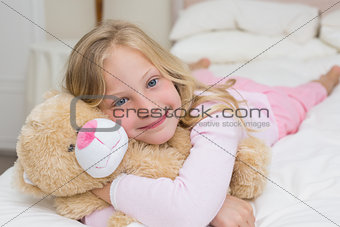 Young girl resting in bed with stuffed toy